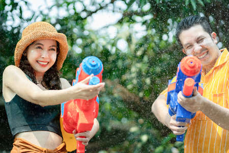 Asian people use water guns to play in the Songkran Festival in Thailand in the summer of April.