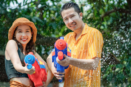 Asian couples play with water guns at Songkran Festival in Thailand in the summer of April. Banco de Imagens