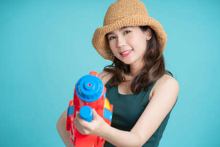 Beautiful woman holding water gun colorful on blue background. She was smiling and happy at the Songkran Festival.