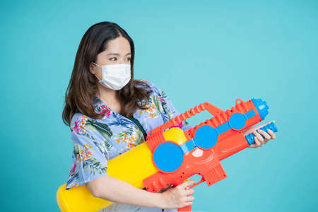 Asian woman wearing protective mask in Songkran festival. She is holding a colorful water gun on a blue background.