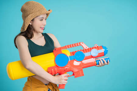 Beautiful woman holding water gun colorful on blue background, Songkran Festival. Banco de Imagens - 165976596