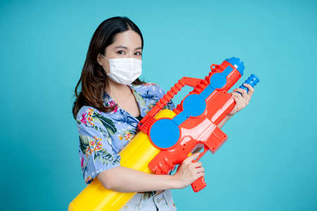 Asian woman wear mask and play with water gun in Songkran Festival. Banco de Imagens