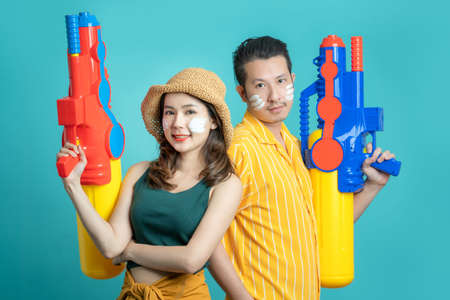 Asian couple playing in the water for Songkran. They are holding a spray gun on isolated blue background. Banco de Imagens