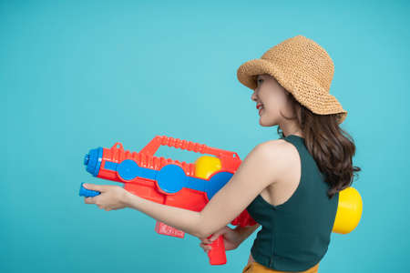 Asian woman use water gun for Songkran. She is standing facing the side.