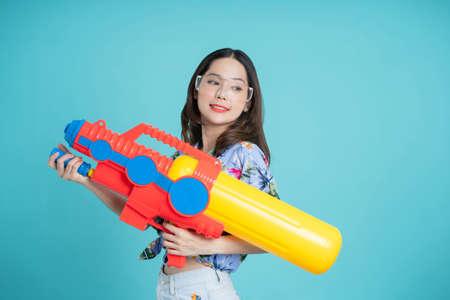 Beautiful woman holding water gun colorful on blue background. Banco de Imagens