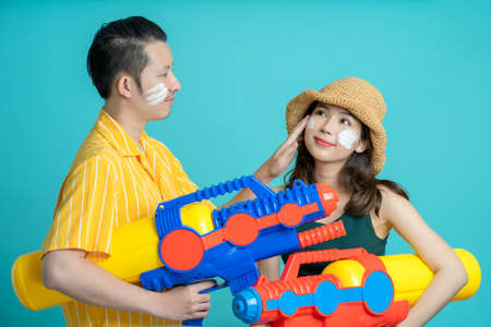 A couple playing in the water in Songkran Festival. They are holding colorful water guns on a blue background.