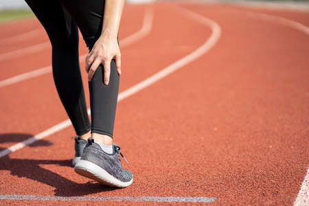 Young Asian woman runner sustained a leg injury from an outdoor run. She has a leg pain. Banco de Imagens