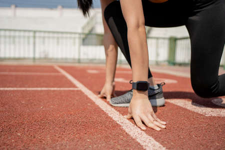 Runner in a stadium is in start position with hands on the line. Hands on starting line. Banco de Imagens