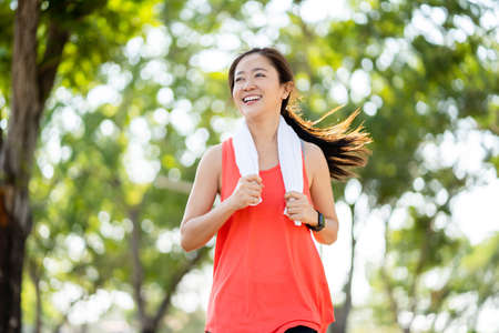 Healthy Asian woman running in the park. She smiled and enjoyed. Banco de Imagens