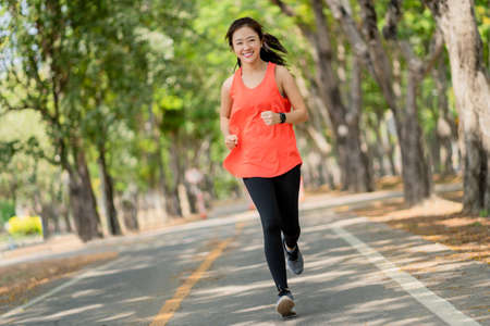Healthy woman are running in the park in the morning. She smiled and enjoyed. Imagens