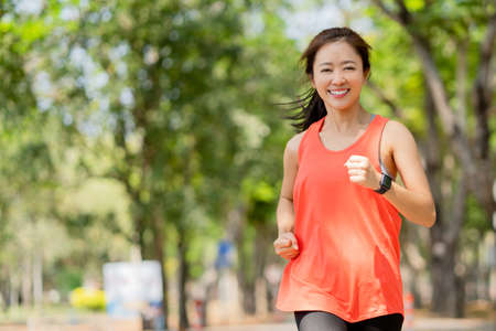 Healthy woman smiling and happy while jogging in the park in the morning. Banco de Imagens