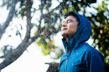 Young Asian man wearing raincoat with rain and clouds. He is very happy. Banco de Imagens