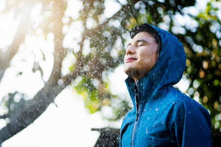 Handsome Asian guy standing in the rain outdoors. He wears a raincoat
