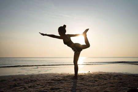 The silhouette of a woman standing on one leg. She practiced yoga on the beach at sunset.