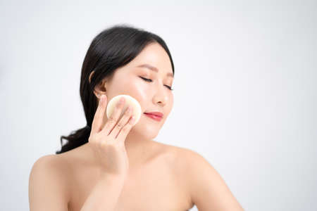 Skin care and healthy treatment of woman removing makeup from face with cotton pad. Isolated on white background.