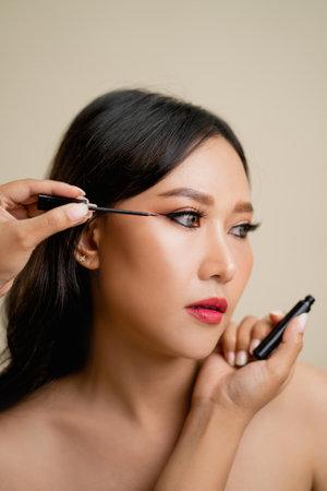 Makeup artist applies eye shadow. Beautiful woman face. Perfect makeup.