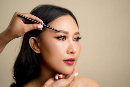 Makeup artist is drawing eyebrows on the face of a beautiful Asian woman. Banco de Imagens