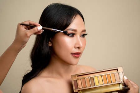 Makeup artist applying eyeshadow powder. Perfect makeup on the face of an Asian woman. Make-up detail.