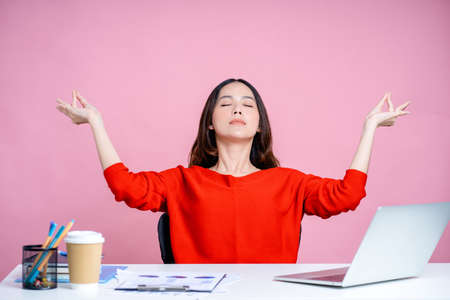 Beautiful woman closed her eyes with meditation, spreading her hands in yoga posture after work at a white desk with a laptop. Isolated on pastel pink background. Banco de Imagens