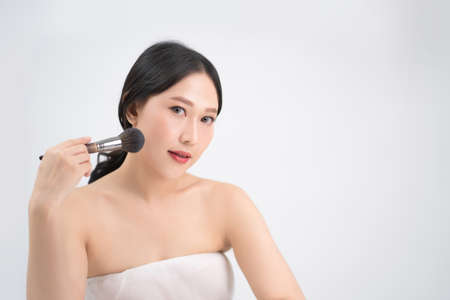 Portrait of a beautiful Asian woman with a makeup brush in hand.