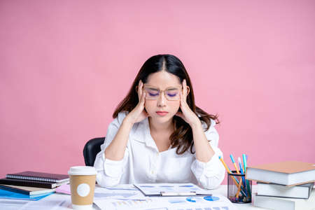 Asian woman working at desk isolated pastel pink background. She was tired from working hard with the laptop.