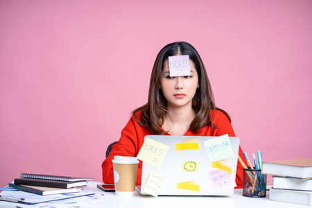 Asian woman working at desk isolated pastel pink background. She was tired of working hard with a sticker on her forehead and using the laptop. Banco de Imagens