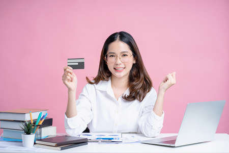 Employees are happy woman in glasses and a white shirt. She was holding a bank credit card and making a winning gesture. Pink background isolated. Career success concept.
