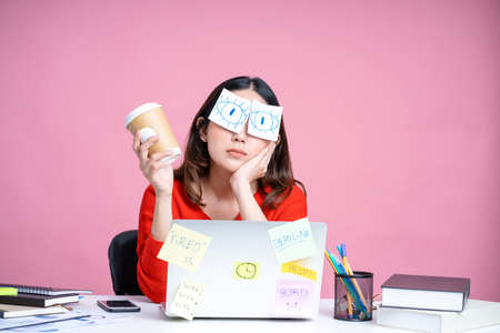 Portraits of overworked Asian women. She was sitting at her desk with stickers covering her eyes and using her laptop on a pastel pink background. Banco de Imagens
