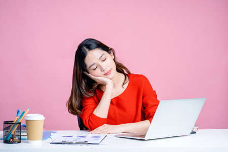 Young Asian woman in a white shirt. She was lying at her desk with a pink background isolated. Banco de Imagens