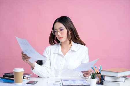 Young Asian woman wearing glasses and a white shirt sits at a white desk. She is holding documents with laptop in the office.Isolated on pastel pink background.