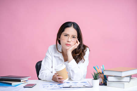 Young Asian businesswoman is tired and upset wearing glasses and white shirt. She is holding hot coffee on the desk with a pink background isolated. Banco de Imagens