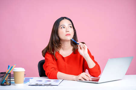 Young Asian woman in casual clothes sits at a white desk with a laptop. She is thinking while working on the table. Isolated pink background.