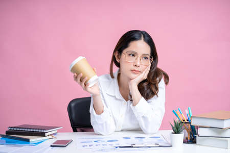 Young Asian woman wearing glasses and white shirt. She was bored with the heavy work that was on the desk and was holding hot coffee. Pink background isolated.