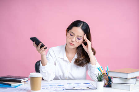 Young Asian woman wearing eyeglasses and a white shirt sits at a white desk with a laptop. She uses her smartphone to type sms messages in the office. Isolated on pastel pink background. Banco de Imagens