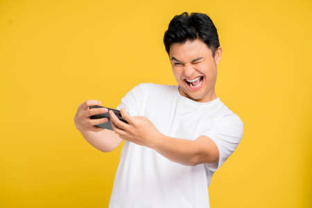 Young Asian man in casual wear is playing games with mobile phone with a yellow background isolated.