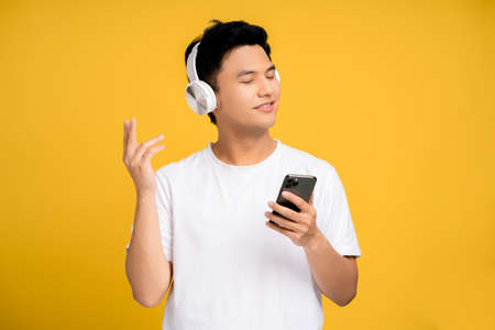 Happy young asian man wearing wireless headphones listening to his favorite music on a smartphone.