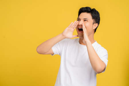Happy young asian man announces information. He is shouting.