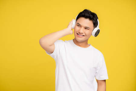 Young Asian man wearing casual clothes and headphones. He is listening to his favorite song with a yellow background isolated. Banco de Imagens