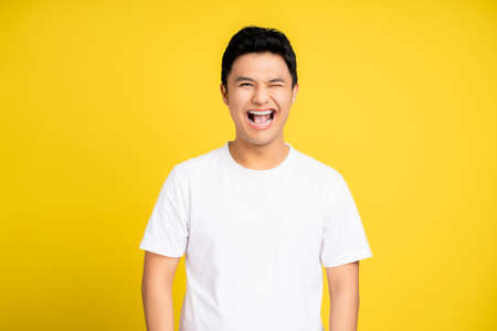 Portrait of smiling and happy Asian young man. He shows emotions and isolated on a yellow background. Banco de Imagens