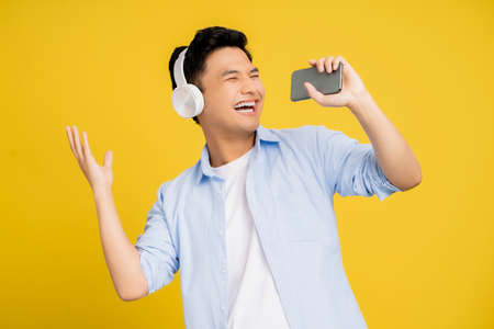 Young Asian man in casual wear. He is wearing headphones and is singing his favorite songs on a yellow studio background.