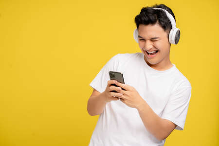 Young Asian man in casual clothes are happy to listen to wireless headphones. He is listening to song on his smartphone on yellow background. Banco de Imagens