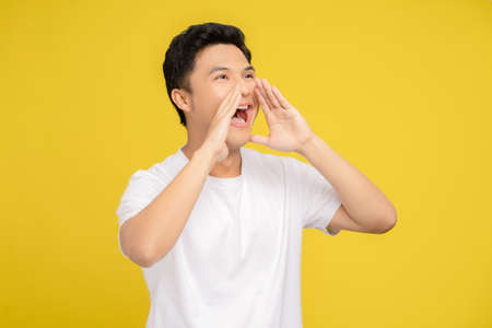 Happy young asian man announces information isolated on yellow background in studio. Banco de Imagens