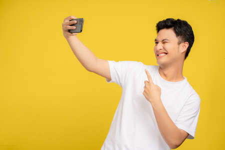 Young Asian man taking a picture with a smartphone. He is very happy.