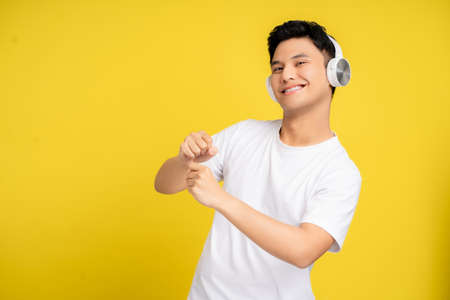Young man dancing and wearing headphones listening to song on yellow studio background.