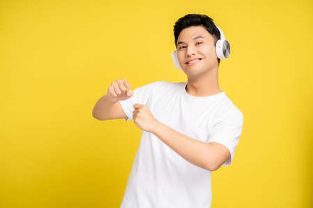Young Asian man smiling and wearing headphones listening to his favorite song. He is happy on the yellow studio background. Banco de Imagens