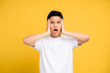 Young Asian man shocked on a yellow background. Isolated background.