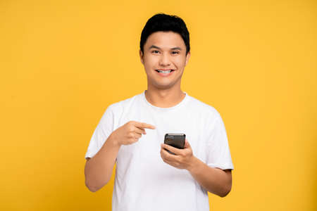 Young Asian man wearing a white T-shirt is using a smartphone. He was smiling and very happy. Isolated background. Banco de Imagens