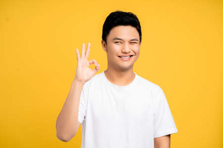 Portrait of of a happy young Asian man showing ok gestures isolated on a yellow background. Banco de Imagens