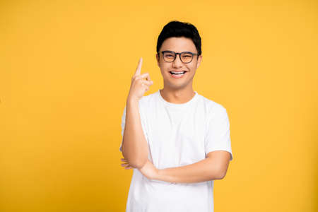 Young Asian man wearing a white T-shirt and glasses. He pointed a finger with a happy face. Isolated background. Banco de Imagens