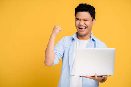 Young Asian man in casual clothes smiling holding a laptop. He shows a winning gesture using his hand and fist on a yellow background.